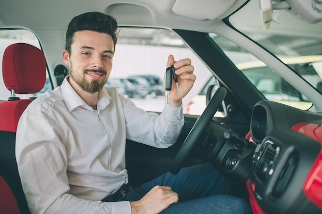 Mano che tiene il telecomando chiave auto, con sfondi di auto moderne. uomo seduto all'interno della nuova auto con le chiavi. Foto Premium