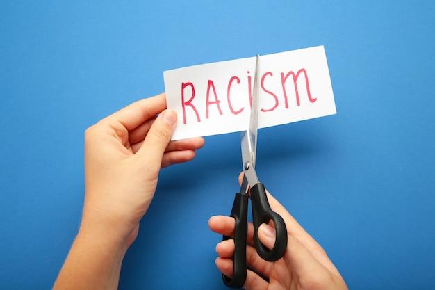 Mano che tiene la carta con il razzismo del testo. vista dall'alto di forbici nere che tagliano la carta di carta con la parola razzismo su sfondo blu. Foto Premium