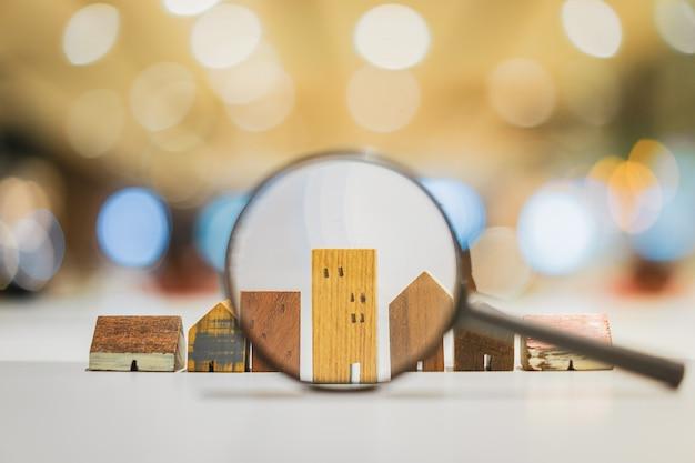 Passi la lente d'ingrandimento della tenuta e l'esame del modello della casa Foto Premium