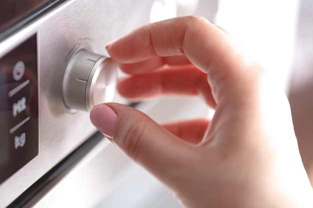 La tenuta della mano gira il calore del bottone del cerchio del quadrante del forno a microonde per la cottura dell'alimento nella stanza della cucina a casa, primo piano. Foto Premium