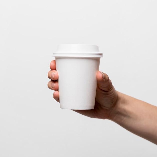 Mano che tiene il primo piano della tazza di caffè bianco Foto Premium