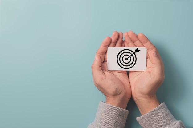 Mano che tiene carta bianca che stampa il bersaglio dello schermo con la freccia su sfondo blu e copia lo spazio, impostare gli obiettivi aziendali e il concetto di destinazione. Foto Premium