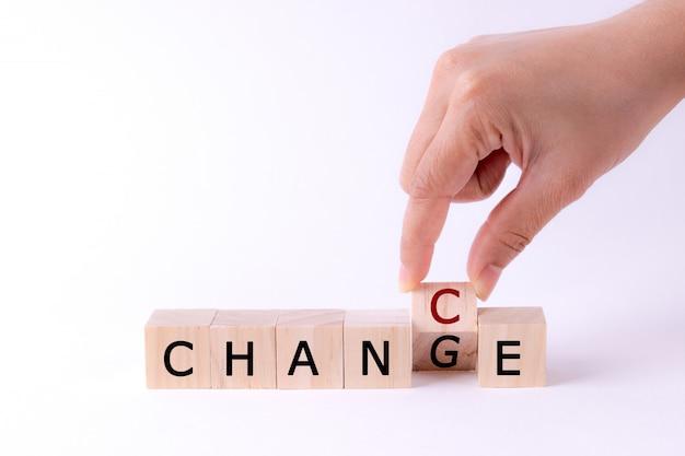 Mano che regge il cubo di legno con il ceppo cambia in change to chance. pensiero positivo. Foto Premium