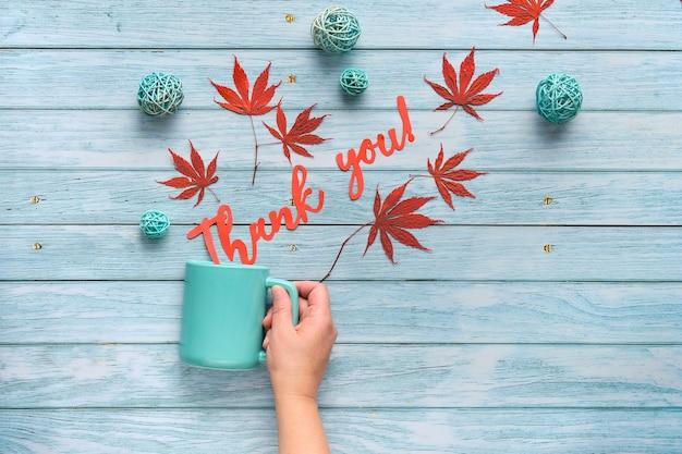 La mano tiene la tazza in ceramica con parole grazie ritagliata di carta. piatto autunnale stagionale con decorazioni autunnali Foto Premium