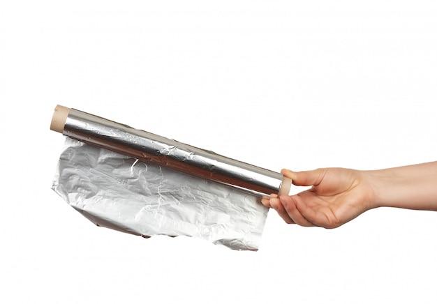 La mano tiene un rotolo con un foglio grigio lucido attorcigliato Foto Premium