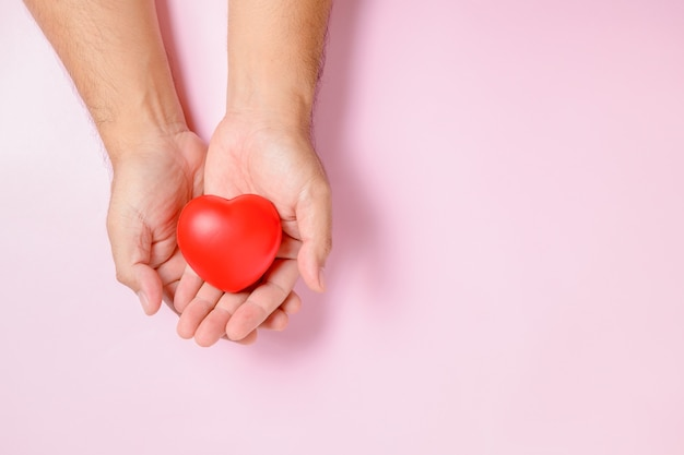 Mano uomo che tiene cuore rosso, donazione, felice beneficenza volontaria, responsabilità sociale csr, giornata mondiale del cuore, giornata mondiale della salute, concetto di giornata mondiale della salute mentale Foto Premium
