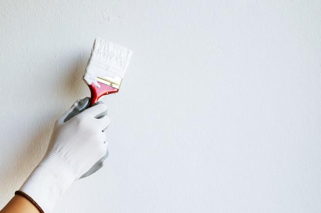 Dipinto a mano un muro bianco con un pennello Foto Premium