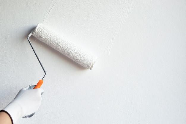 Dipinto a mano un muro bianco con un rullo di vernice Foto Premium