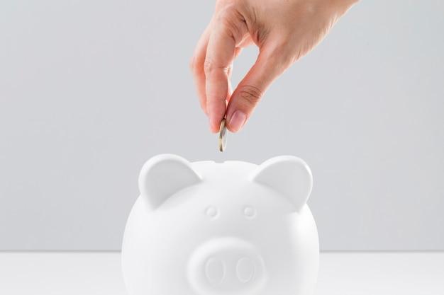 Mano mettendo le monete nel salvadanaio Foto Premium