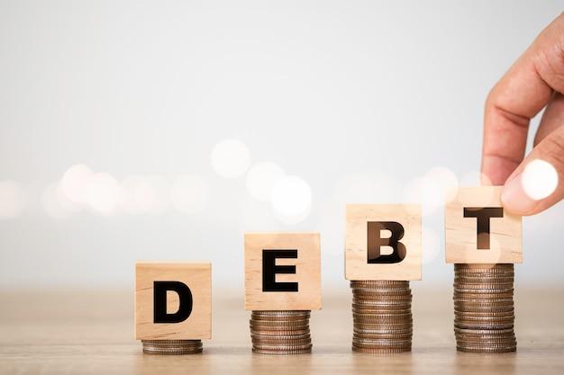 Mano mettendo la formulazione del debito che sono stampati a cubi di legno sull'impilamento delle monete. concetto crescente di debito. Foto Premium