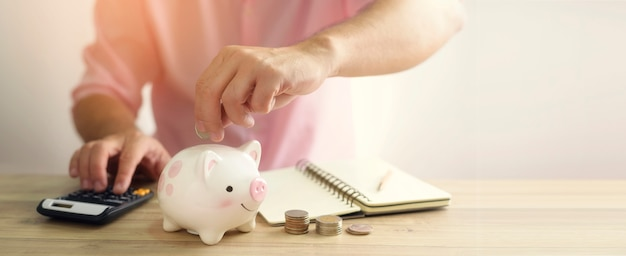 Una mano che mette soldi moneta nel salvadanaio. un risparmio per il futuro concetto di investimento. Foto Premium