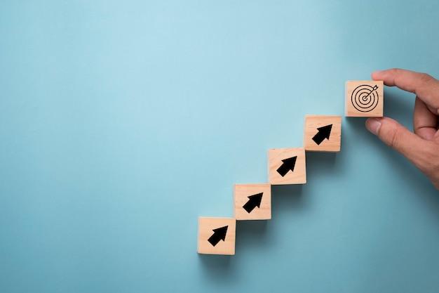 Passi mettere il bersaglio virtuale e la freccia che stampano lo schermo sul cubo di legno. obiettivo di successo aziendale e concetto di obiettivo obiettivo. Foto Premium