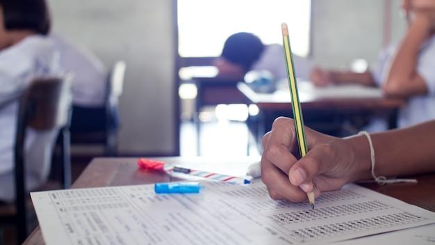 Mano di studenti che scrivono e sostengono l'esame con lo stress in classe Foto Premium