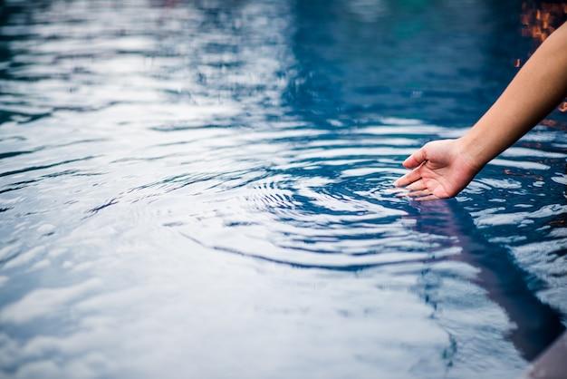 La mano che tocca l'acqua blu. la piscina è pulita e luminosa. con una goccia d'acqua o Foto Premium