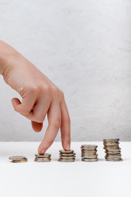 Mano che cammina sul concetto di monete Foto Premium
