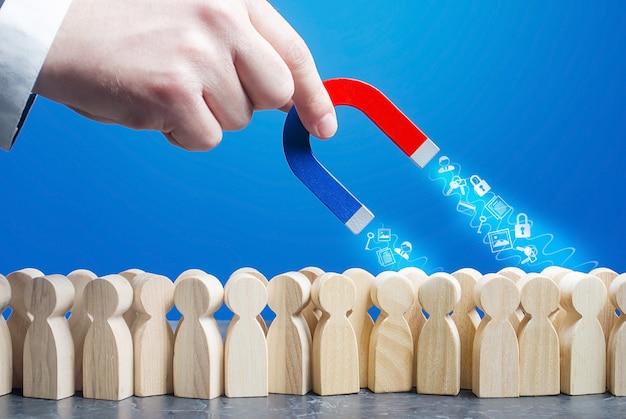 La mano con un magnete raccoglie i dati personali dagli utenti di internet in linea di figure della folla. Foto Premium
