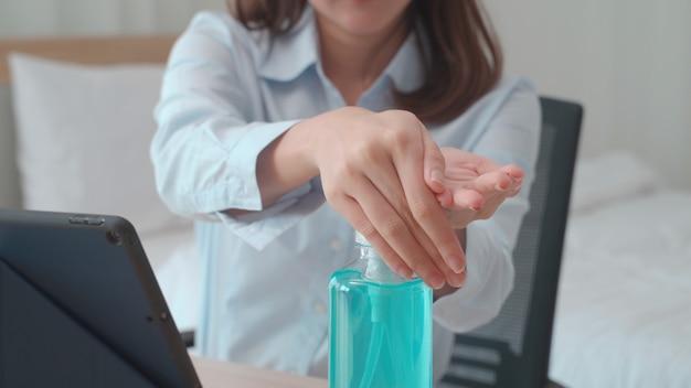 Mano della donna che preme il gel dell'alcool dalla bottiglia e che applica il gel disinfettante per il lavaggio delle mani per pulire e eliminare germi, batteri e virus. protezione pandemica, concetto igienico e sanitario. Foto Premium
