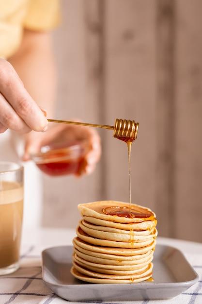 Mano di giovane casalinga in piedi a tavola e mettendo miele fresco in cima alla pila di frittelle mentre cucina la colazione per la sua famiglia in cucina Foto Premium