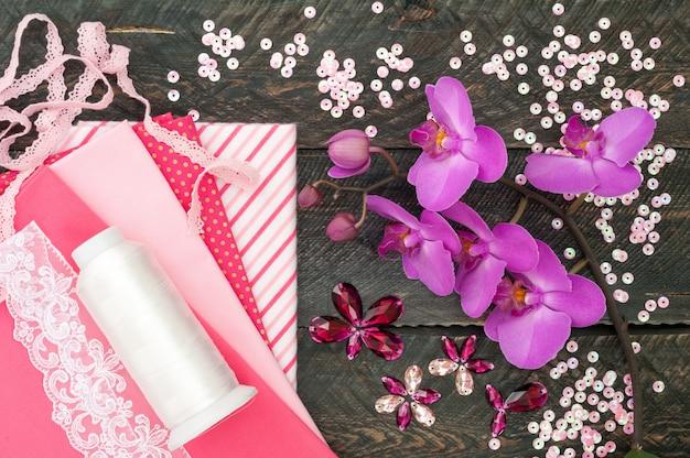 Accessori fatti a mano. tessuto di cotone, pizzo, filo della bobina, cristalli e paillettes per ricamo su fondo in legno vecchio. fiori di orchidea Foto Premium