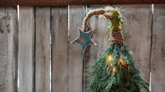 Albero di natale fatto a mano con una stella su una parte superiore curva su uno sfondo di legno. capodanno economico. stile eco moderno minimalista. Foto Premium