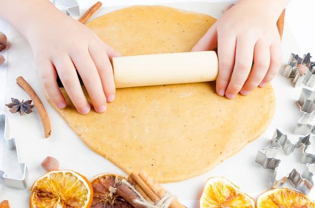 Mani di un bambino con un mattarello su un impasto per biscotti di panpepato di natale, Foto Premium