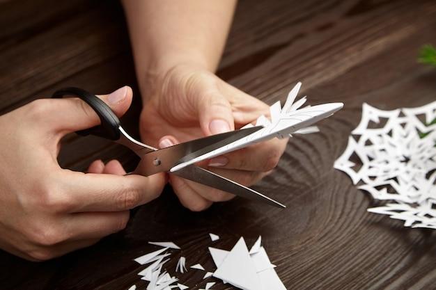 Mani che tagliano i fiocchi di neve del libro bianco sulla tavola di legno Foto Premium