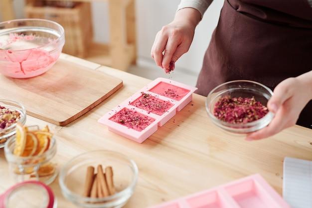 Mani di donne che spruzzano petali floreali grattugiati secchi sopra le saponette rosa fatte a mano in stampi in silicone durante la master class Foto Premium