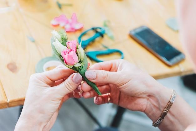 Mani di un fioraio che fa boutonnieres Foto Premium