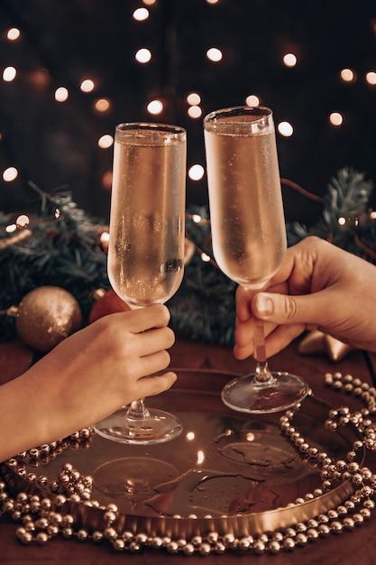 Le mani tengono bicchieri di champagne e controllano tra le luci di natale. Foto Premium