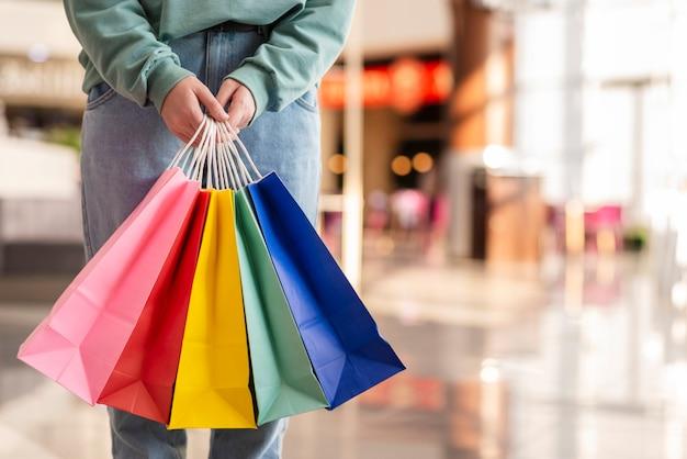 Mani in possesso di sacchi di carta colorata Foto Premium