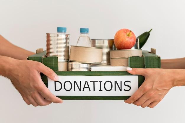 Mani che tengono la casella di donazione con il cibo Foto Premium