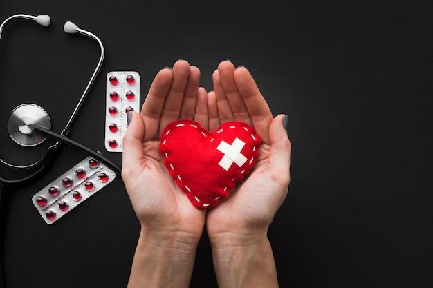 Mani che tengono cuore e pillole con lo stetoscopio su fondo Foto Premium