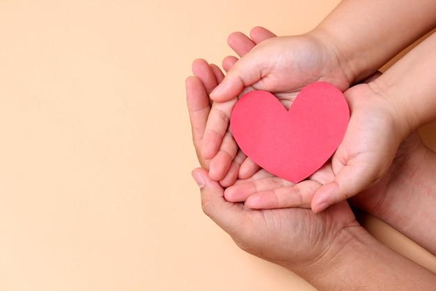 Mani che tengono il cuore di carta rosso, concetto di salute in famiglia. Foto Premium