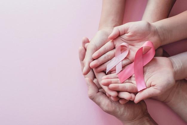 Mani che tengono i nastri rosa su fondo rosa Foto Premium