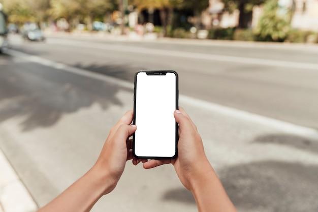 Mani che tengono smartphone con mock-up Foto Premium