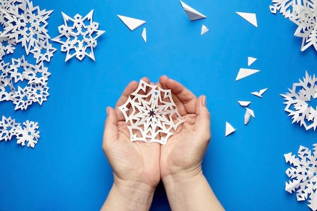 Mani che tengono il fiocco di neve di carta tagliata bianca sulla superficie blu Foto Premium