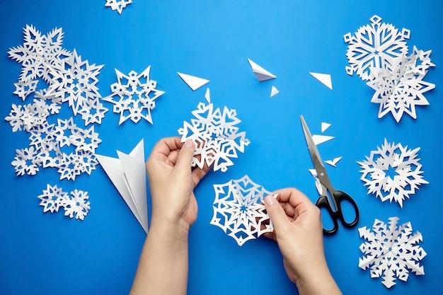 Mani che tengono i fiocchi di neve di carta tagliati bianchi sulla superficie blu Foto Premium