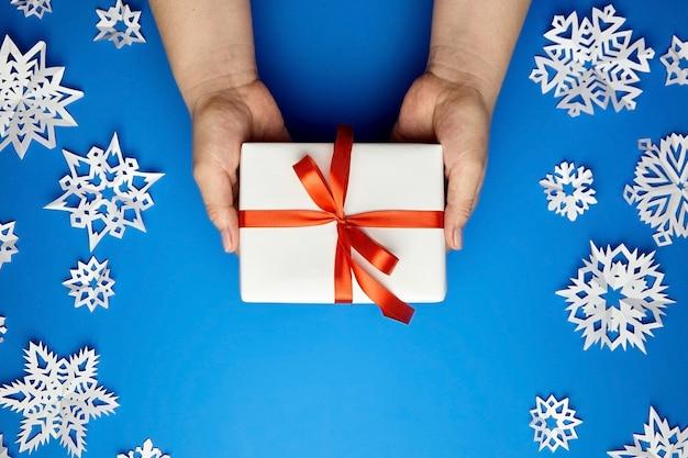 Mani che tengono il contenitore di regalo bianco con il nastro rosso sull'azzurro con i fiocchi di neve di carta Foto Premium
