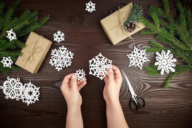 Mani che tengono il fiocco di neve del libro bianco sulla tavola di legno Foto Premium