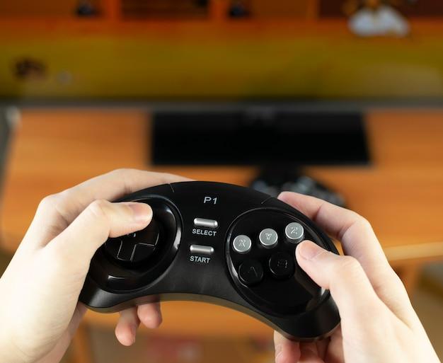 Mani che tengono un joystick retrò senza fili Foto Premium