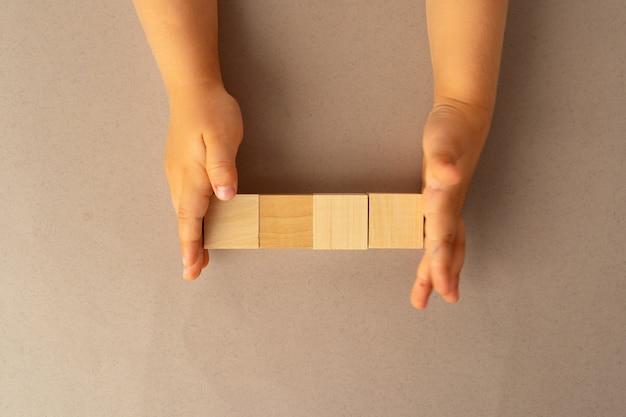 Mani di un bambino con quattro blocchi di legno, vista dall'alto Foto Premium