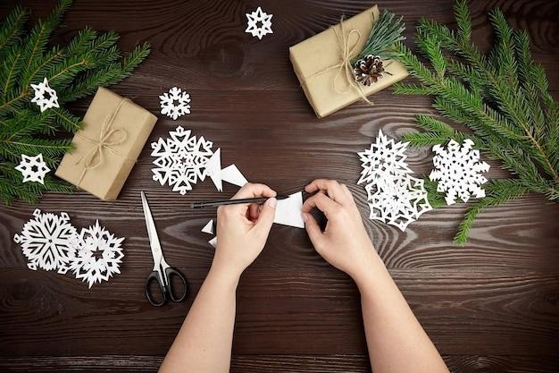 Mani che fanno i fiocchi di neve di carta bianca sulla tavola di legno Foto Premium