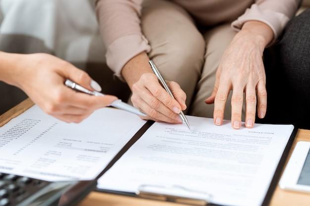 Mani del cliente maturo e dell'agente immobiliare con le penne che indicano il contratto prima di firmarlo Foto Premium