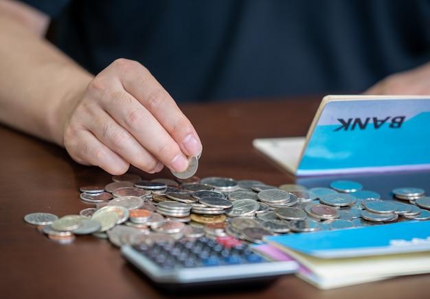 Le mani degli uomini che hanno in mano un libretto di banca e tessono un bilancio. Foto Premium