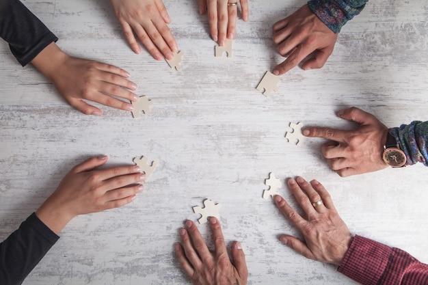 Mani di persone che tengono puzzle. partnership, successo, lavoro di squadra Foto Premium