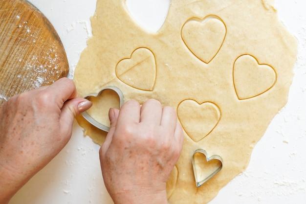 Mani che premono la taglierina del biscotto a forma di cuore nell'impasto Foto Premium