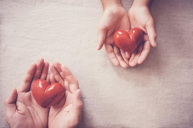 Mani e cuore rosso, assicurazione sanitaria, donazione e concetto di beneficenza Foto Premium