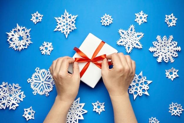 Mani che legano nastro rosso su confezione regalo bianca su blu con fiocchi di neve di carta Foto Premium