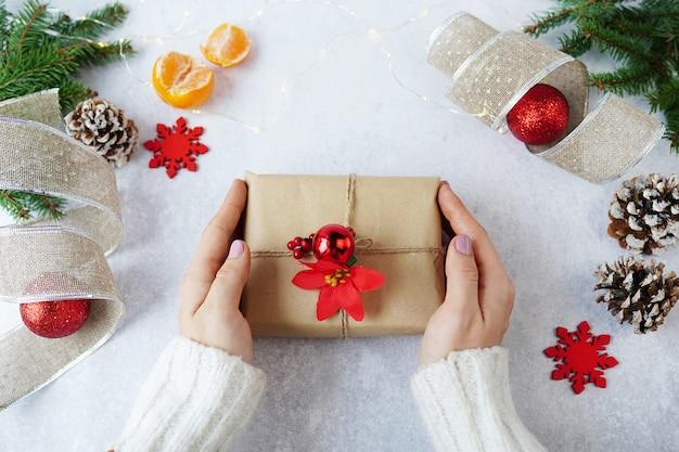 Mani della donna che tiene il contenitore di regalo di natale con decorazioni invernali Foto Premium