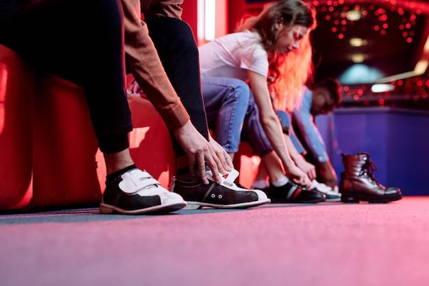 Mani del giovane uomo in abbigliamento casual che indossa scarpe per giocare a bowling mentre è seduto sulla panchina sul muro dei suoi amici Foto Premium
